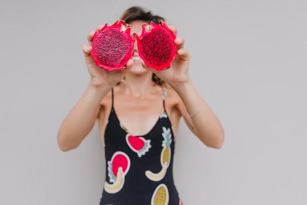 Unscharfes porträt der lustigen gebräunten frau mit roter pitaya im fokus. innenporträt des anmutigen mädchens im schwarzen kleid, das drachenfrüchte hält.