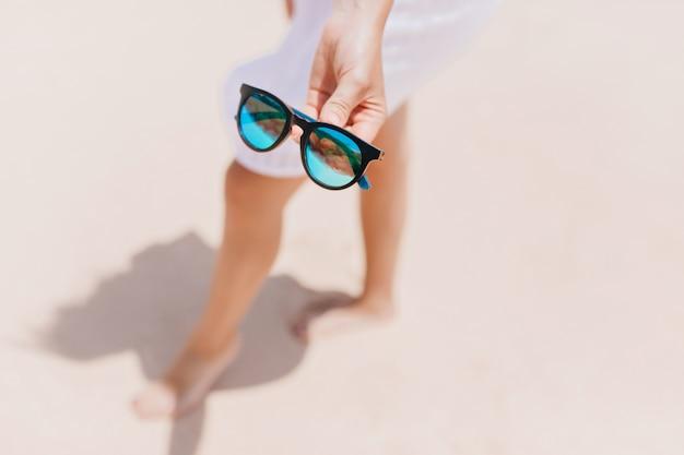 Unscharfes porträt der wohlgeformten dame, die auf sand im weißen kleid steht. außenaufnahme der kaukasischen gebräunten frau, die am strand kühlt und sonnenbrille hält.