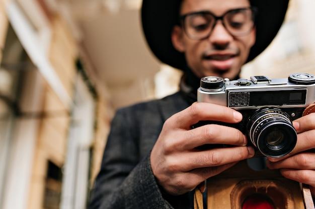 Unscharfes porträt des konzentrierten afrikanischen fotografen lokalisiert auf stadtstraße. außenfoto des stilvollen schwarzen mannes mit der kamera im fokus.