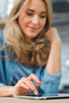 Unscharfes Porträt einer jungen Frau, die digitale Tablette verwendet