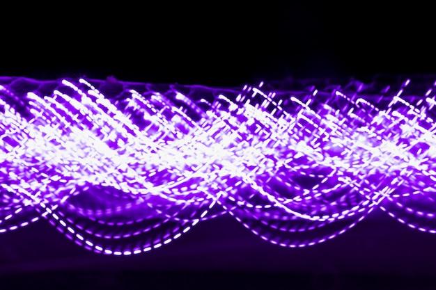 Unscharfes purpurrotes dekoratives licht auf schwarzem hintergrund