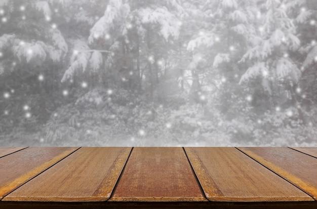 Unscharfes schneien im kiefernwald durch glasfensterhintergrund mit hölzerner tabelle.