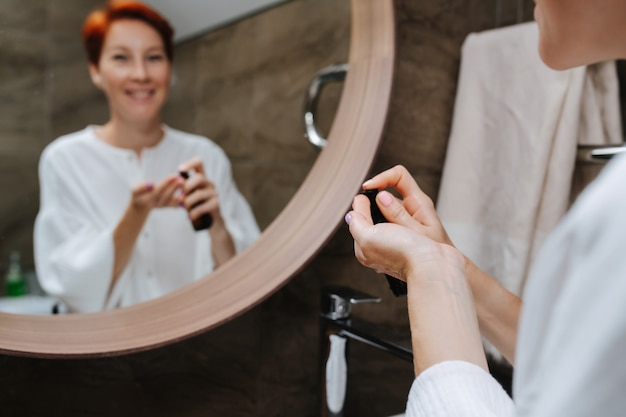 Unscharfes spiegelbild einer reifen frau, die kosmetik auf ihre hand legt, um sie aufzutragen. ihre hände im vordergrund.