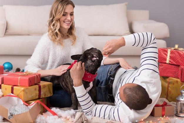 Unser familienmitglied. gut aussehendes positives glückliches paar, das zwischen geschenkboxen sitzt und mit ihrem hund spielt, während der weihnachtsmorgen genießt