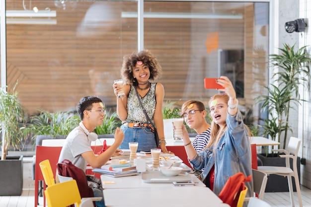 Unser geburtstagskind. glückliche brünette frau, die glas in der rechten hand hält, während zeit mit ihren klassenkameraden verbringt