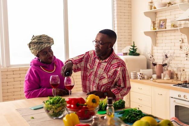 Unser jahrestag. positives freudiges paar, das rotwein trinkt, während es ihr jubiläum feiert