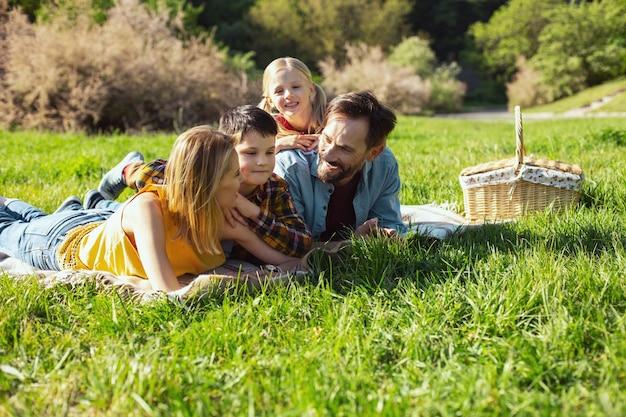 Unser picknick. fröhlicher bärtiger papa, der mit seiner familie lächelt und auf der decke liegt