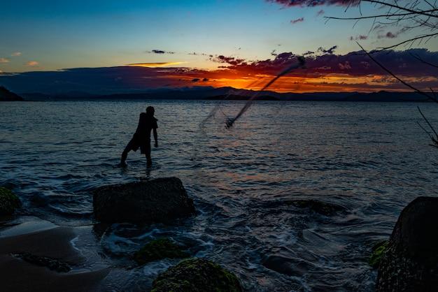 Unser täglicher fisch. silhouette eines fischers, der das fischernetz