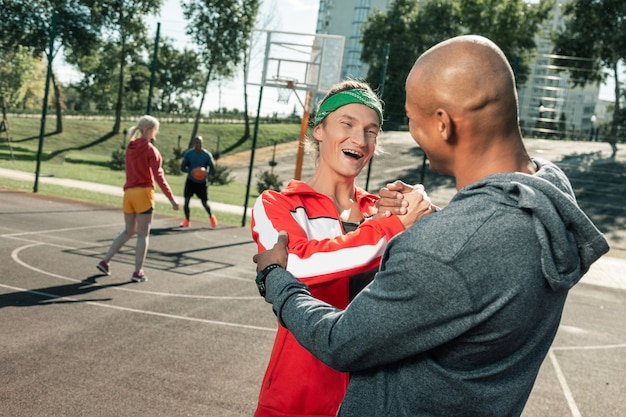 Unser treffen. erfreute männliche freunde grüßen sich gegenseitig, während sie kommen, um basketball zu spielen