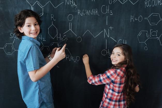 Unser wissen anwenden. fähige, kluge kleine schüler, die in der schule sitzen und den chemieunterricht genießen, während sie sich notizen an die tafel machen und lächeln