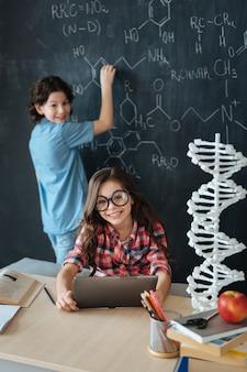 Unsere fähigkeiten anwenden. glückliche kluge kleine schüler, die in der schule sitzen und chemieunterricht genießen, während notizen machen und tablette verwenden