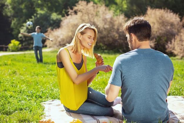 Unsere freizeit. fröhliche blonde frau, die mit ihrem ehemann und ihrem kind spricht, die im hintergrund spielen