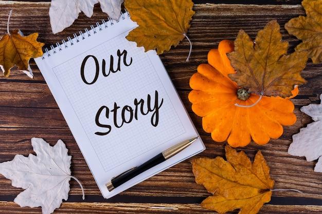 Unsere geschichte, inschrift, text ist in einem weißen notizbuch mit einem stift geschrieben. herbst, ahorn, blätter und alte bretter.
