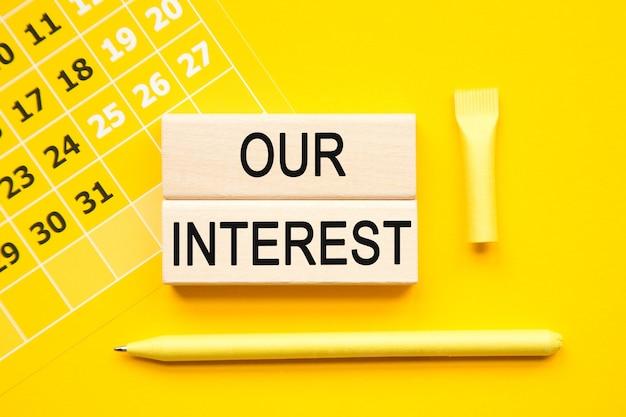 Unsere interesse inschrift auf würfeln, abstrakter kalender, gelber stift auf gelbem hintergrund. eine helle lösung für das geschäfts-, finanz- und marketingkonzept