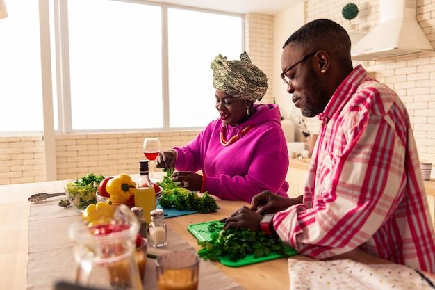 Unsere küche. freudiges afrikanisches paar, das sein traditionelles gericht beim mittagessen zubereitet