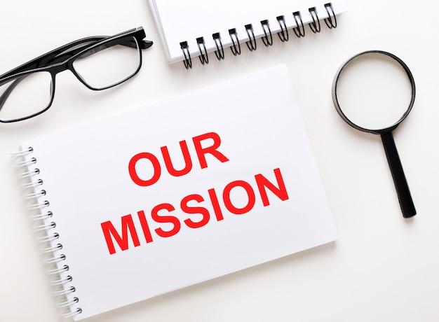 Unsere mission ist in einem weißen notizbuch auf hellem hintergrund in der nähe des notizbuchs geschrieben