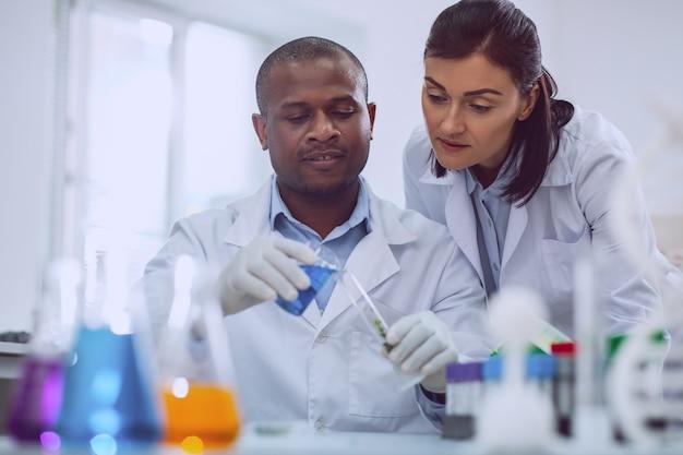 Unsere neue forschung. inspirierter afroamerikanischer wissenschaftler, der einen test durchführt, und sein kollege, der in seiner nähe steht