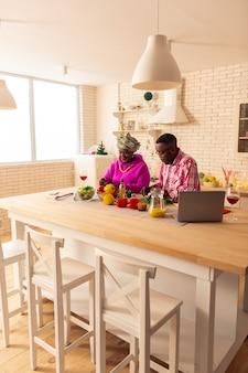 Unsere traditionen. angenehmes afrikanisches paar, das in der küche ist, während es sein traditionelles essen kocht
