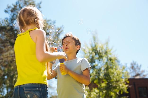 Unsere unterhaltung. alarmieren sie entzückende kinder, die spaß haben und seifenblasen blasen