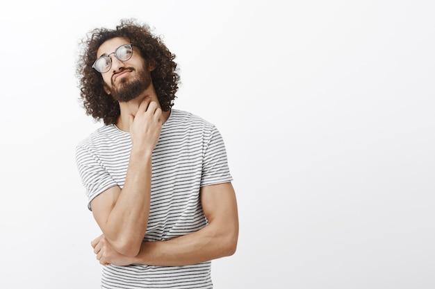Unsicher verwirrter attraktiver spanischer typ mit stilvollem lockigem haarschnitt in brille, kopf nach oben geneigt und hals kratzend, denkend, befragt