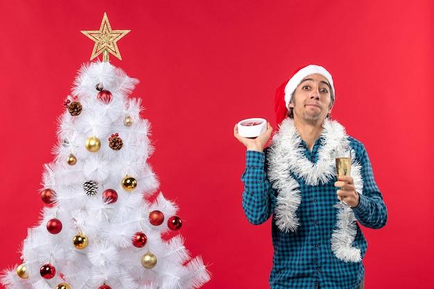 Unsicher verwirrter junger mann mit weihnachtsmannhut, der ein glas wein hebt und die uhr stehend hält
