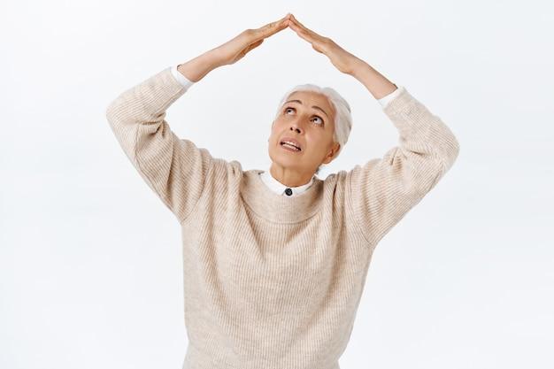 Unsichere und neugierige ältere dame, großmutter, die mit den händen über dem kopf eine dachgeste macht, unsicher aussieht und gefragt wird, ob regen fällt, weiße wand in süßem outfit stehend