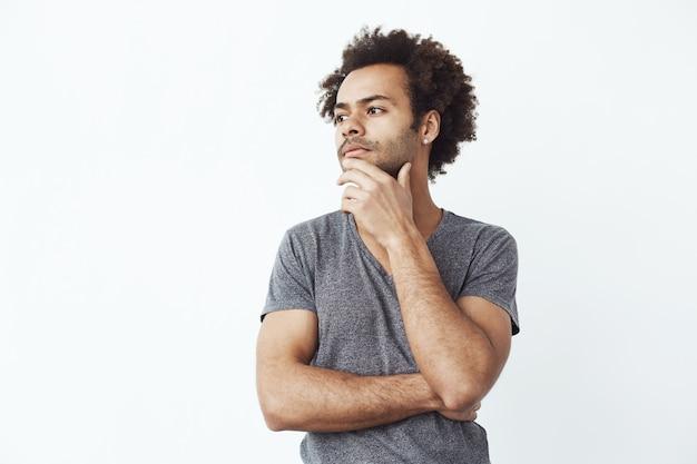 Unsicherer afrikanischer mann, der denkt, in seite über weiße wand schauend, entscheidet, ob man einige geräte online kauft oder ein student, der versucht, sich an eine partei zu erinnern.