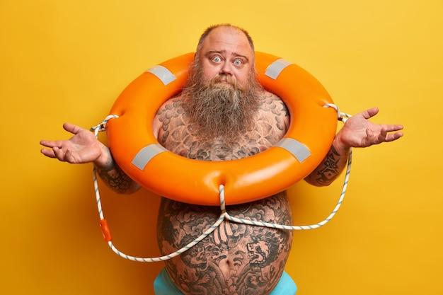 Unsicherer bärtiger mann mit großem tätowiertem bauch, spreizt die hände zur seite, fühlt sich zweifelhaft und zögernd, steht in einem orangefarbenen rettungsring, lernt schwimmen, isoliert auf gelber wand. zeit zum schwimmen