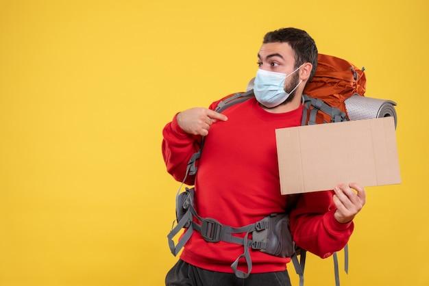 Unsicherer junger mann, der eine medizinische maske mit rucksack trägt und ein blatt hält, ohne zu schreiben, dass er auf gelb zeigt
