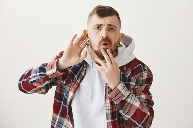 Unsicherer junger mann kann nichts hören, hör genauer zu