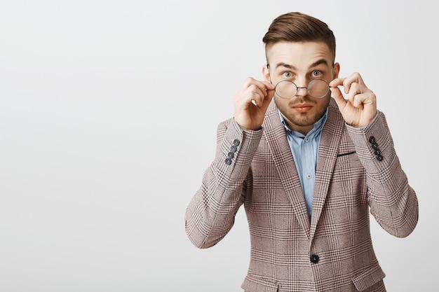 Unsicherer nerdiger kerl in brille und anzug, der schüchtern und misstrauisch aussieht