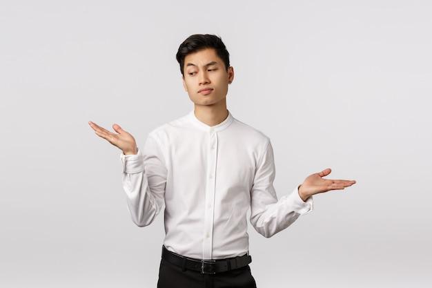 Unsicherer, skeptischer stilvoller asiatischer männlicher unternehmer, büroangestellter, der entscheidung trifft, die hände seitlich anhebt, verblüfft und zögernd aussieht, die stirn runzelt und sich die mühe macht, eine wahl zu treffen