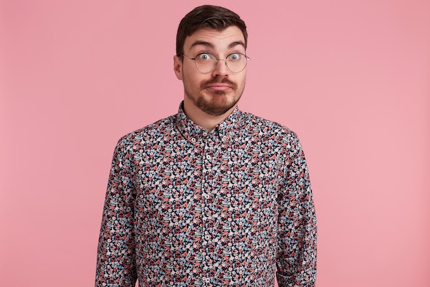Unsicherer unsicherer überraschter mann starrt durch brillen, die buntes hemd mit den schultern zucken, unsicher über rosa hintergrund