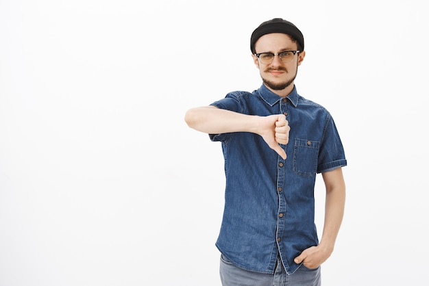 Unsicherer unzufriedener süßer junger mann in schwarzer mütze und brille, der grinst und daumen nach unten zeigt, weil er es nicht mag, mit freunden uneinigkeit auszudrücken, während er über das thema spricht