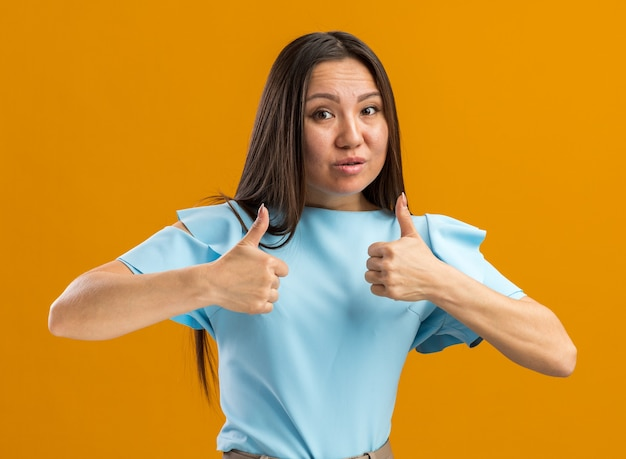 Unsicheres junges asiatisches mädchen, das die kamera betrachtet, die daumen hoch isoliert auf oranger wand mit kopienraum hält