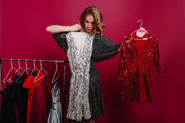 Unsicheres junges weibliches modell, das kleiderbügel mit zwei kleidern hält und sich auf party vorbereitet