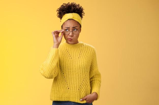Unsicheres nachdenkliches zögerliches süßes afroamerikanisches tausendjähriges teenager-mädchen in runder brille, pullover, stirnband, das rätsel löst, schauen zweifelhafte berührungsbrillen grinsend auf und denken gelber hintergrund.