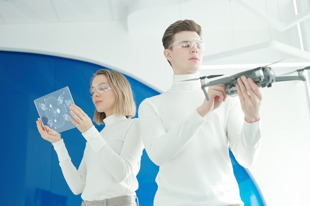 Unten ansicht der jungen frau, die drohnenaufbauten auf futuristischem tablett analysiert, während männlicher ingenieur drohne untersucht