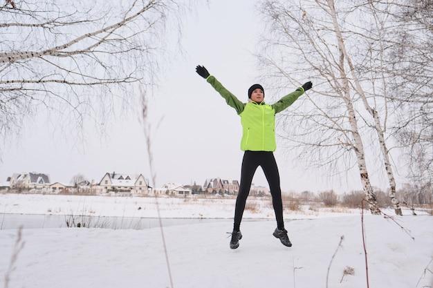 Unten ansicht der jungen frau, die dynamische übung für arme und beine im winterwald praktiziert