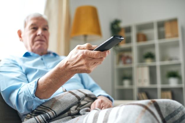 Unten ansicht des älteren mannes mit warmem plaid auf den beinen, die kanäle mit fernbedienung wechseln, während sie zu hause fernsehen