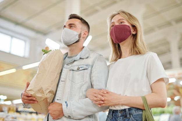 Unten ansicht des jungen paares in den gesichtsmasken, die zusammen über bauernmarkt während coronavirus gehen und lebensmittel kaufen