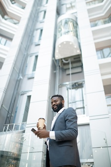 Unten ansicht des lächelnden jungen schwarzen geschäftsmannes mit smartphone, der kaffee auf bewegung trinkt