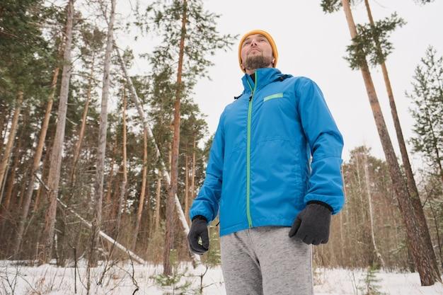 Unten ansicht des nachdenklichen jungen mannes mit stoppeln, die warme kleidung tragen, die im winterwald gehen