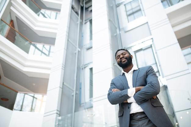 Unten ansicht des positiven erfolgreichen schwarzen geschäftsmannes mit bart, der mit verschränkten armen in der bürohalle steht