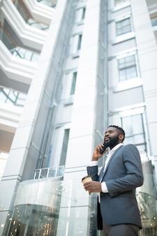 Unten ansicht des selbstbewussten bärtigen geschäftsmannes im anzug, der kaffee trinkt und während der arbeit am umzug per telefon spricht