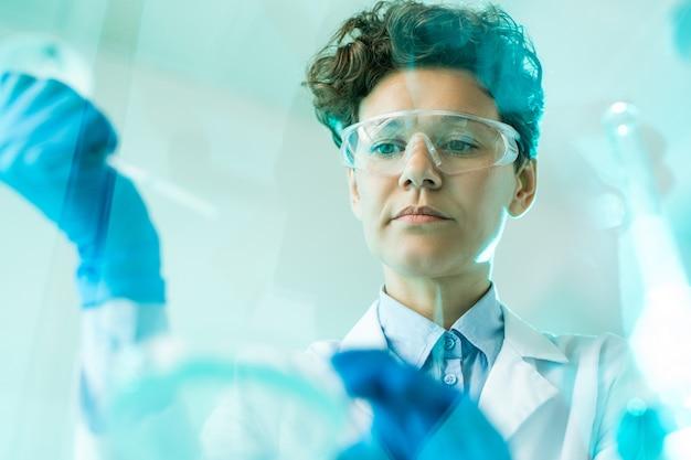 Unten ansicht einer konzentrierten wissenschaftlerin in schutzbrillen, die mit proben im labor arbeitet