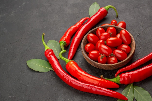 Unten ansicht halbkreis von roten peperoni und lorbeerblättern und eine schüssel kirschtomaten auf der rechten seite des schwarzen tisches