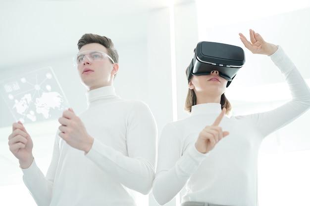 Unten ansicht junger entwickler, die virtual-reality-simulator und futuristisches tablet synchronisieren