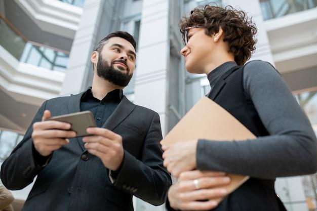 Unten ansicht von jungen ehrgeizigen geschäftspartnern in abendgarderobe, die projekt mit smartphone im büro diskutieren