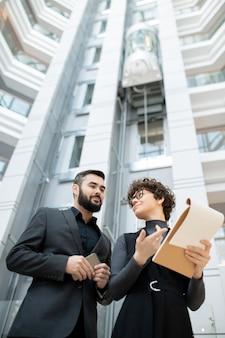 Unten ansicht von projektmanagern, die in der bürolobby stehen und papier mit schätzung prüfen